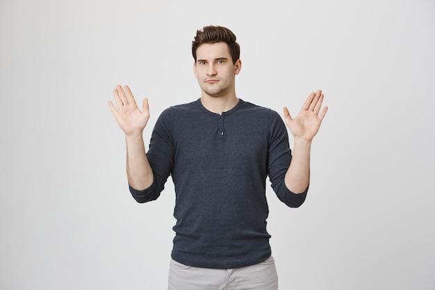 Poważny niechętny mężczyzna pokazuje ręce do góry i poddaje się