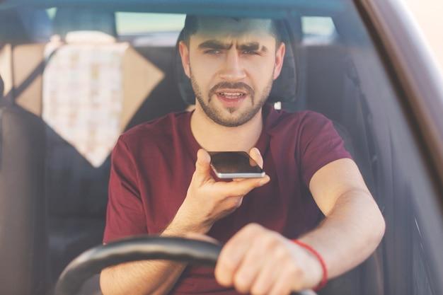 Poważny, nieogolony, brunet kieruje samochodem, wykonuje połączenia głosowe, rozmawia z kolegą, idzie do pracy, stoi w korku