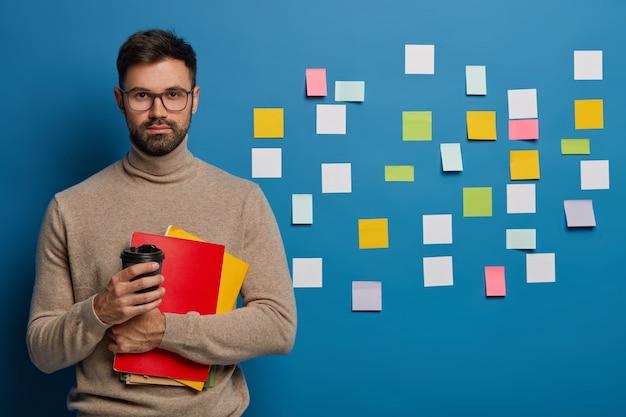 Poważny nieogolony mężczyzna pije kawę na wynos, kolorowe puste naklejki na ścianie, pije kawę z papierowego kubka, trzyma notesy