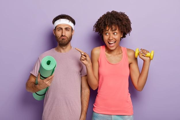 Poważny nieogolony mężczyzna trzyma karemat, gotowy do treningu, a kobieta wskazuje palcem wskazującym na bok