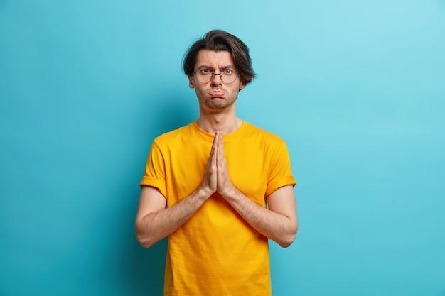 Poważny niezadowolony europejczyk ściska dłonie i prosi o coś, czyniąc modlący się gest