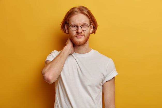 Poważny niezadowolony mężczyzna z fryzurą typu bob, rudą brodą, dotknięciem szyi