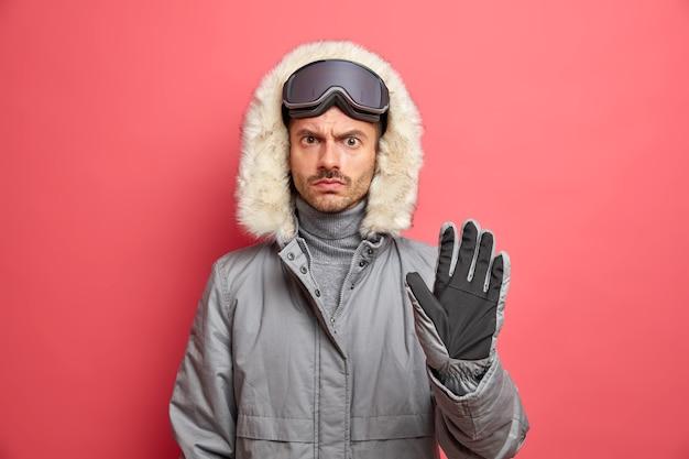 Poważny niezadowolony narciarz w zimowym ubraniu nosi gogle narciarskie, a na głowie trzyma dłoń skierowaną do przodu, wykonując gest stop.