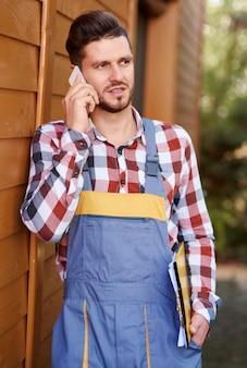 Poważny ogrodnik rozmawia przez telefon komórkowy