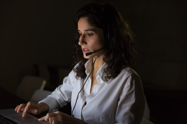 Poważny operator call center w ciemnym biurze