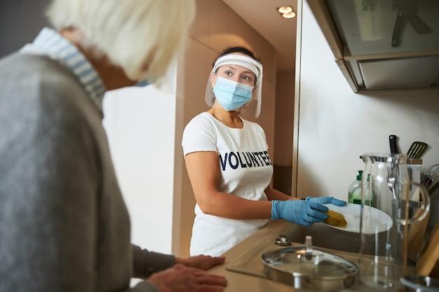 Poważny opiekun w lateksowych rękawiczkach i osłonie twarzy pomagający samotnej kobiecie w pracach domowych