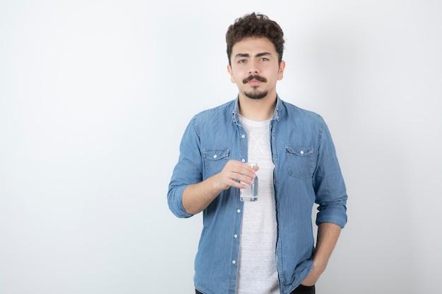 Poważny patrząc mężczyzna trzyma szklankę wody na białym tle.