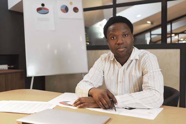 Poważny, pewny siebie afrykański dyrektor generalny w formalnej koszuli w paski siedzi w sali konferencyjnej