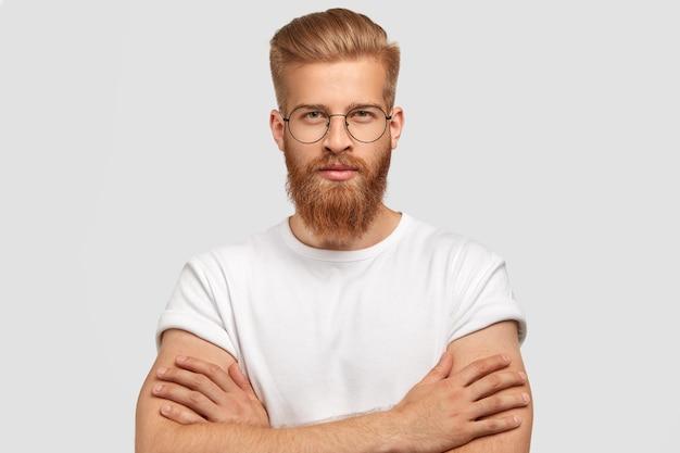 Poważny, pewny siebie architekt trzyma ręce skrzyżowane, ma gęstą rudą brodę i wąsy