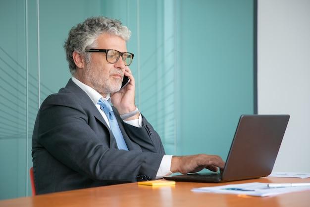 Poważny pewny siebie biznesmen w garniturze i okularach rozmawia przez telefon komórkowy, pracuje przy komputerze w biurze, używając laptopa przy stole z papierowymi diagramami