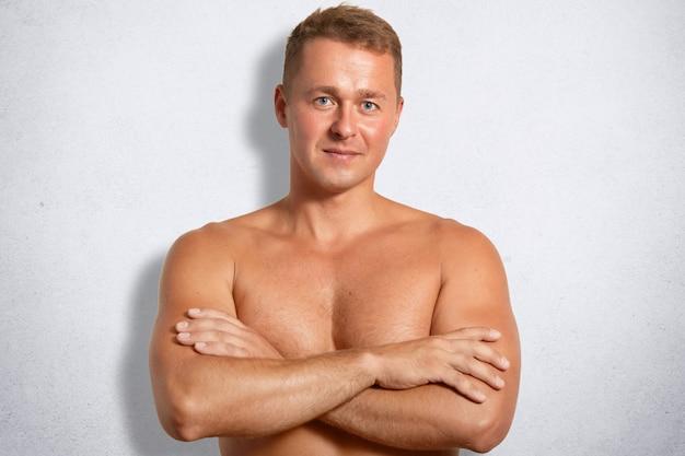 Poważny, pewny siebie mężczyzna o muskularnym ciele, trzyma skrzyżowane ręce, stoi nagi na białej betonowej ścianie