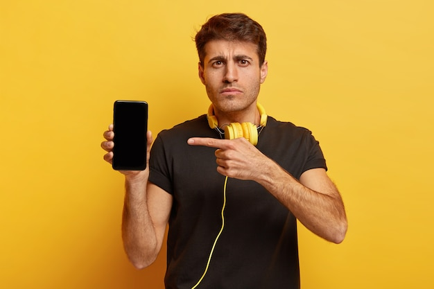 Poważny pewny siebie mężczyzna wskazuje na nowoczesny smartfon z makietą ekranu