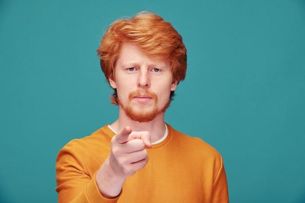 Poważny, pewny siebie młody rudy mężczyzna z brodą, wskazujący na ciebie, zadając pytanie