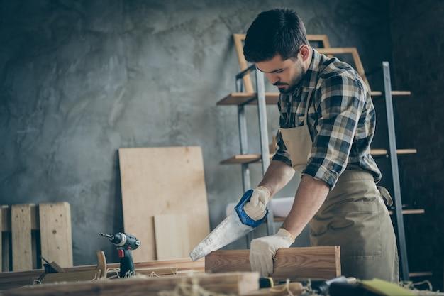 Poważny, pewny siebie, skoncentrowany mężczyzna z profilu bocznego odcinający za pomocą piły niepotrzebne kawałki drewnianego bloku