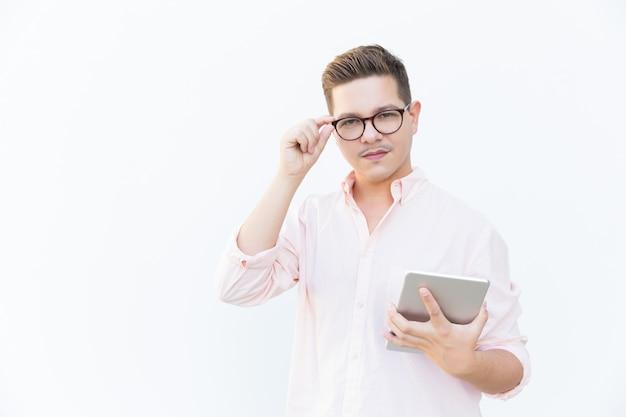 Poważny, pewny siebie twórca aplikacji trzyma tablet