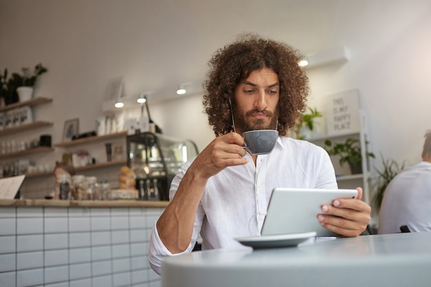 Poważny piękny brodaty facet z kręconymi brązowymi włosami siedzi przy stole w kawiarni i pije kawę, trzymając tablet w dłoni i nosząc słuchawki