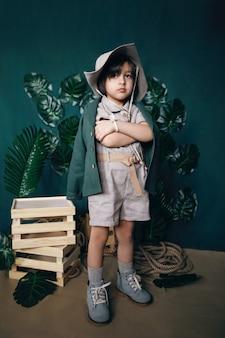 Poważny podróżnik dziecko chłopiec w kapeluszu stanąć na drewnianych skrzyniach w studio na zielonym tle