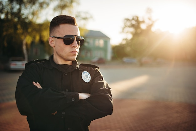 Poważny policjant w mundurze i okularach przeciwsłonecznych