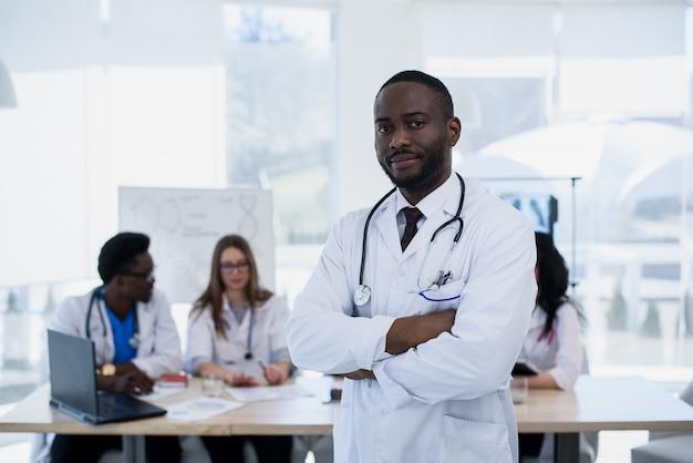 Poważny portret lekarza afroamerykanów. portret medyczny asystent z stetoskopem. samiec lekarka z grupą medyczną przy szpitalem.