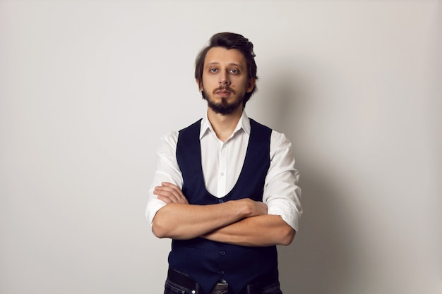 Poważny portret mężczyzny w kamizelce w białej koszuli na białej ścianie