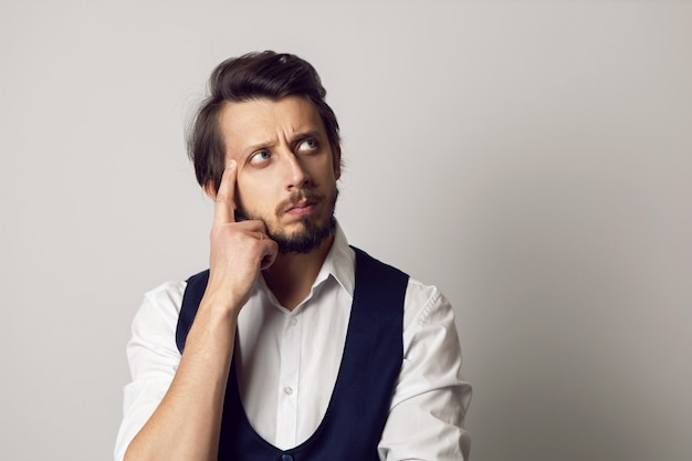 Poważny Portret Mężczyzny W Kamizelce W Białej Koszuli Na Białej ścianie Premium Zdjęcia