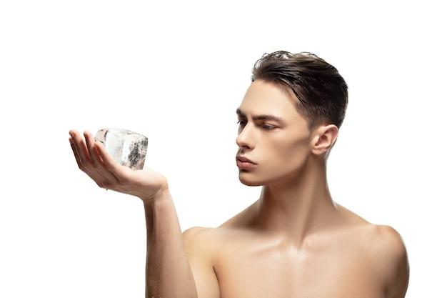 Poważny. portret młodego mężczyzny na białym tle na tle białego studia. kaukaski atrakcyjny model męski. pojęcie mody i urody, samoopieki, pielęgnacji ciała i skóry. przystojny chłopak o zadbanej skórze.