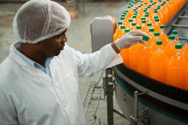 Poważny pracownik płci męskiej bada butelki w fabryce soków