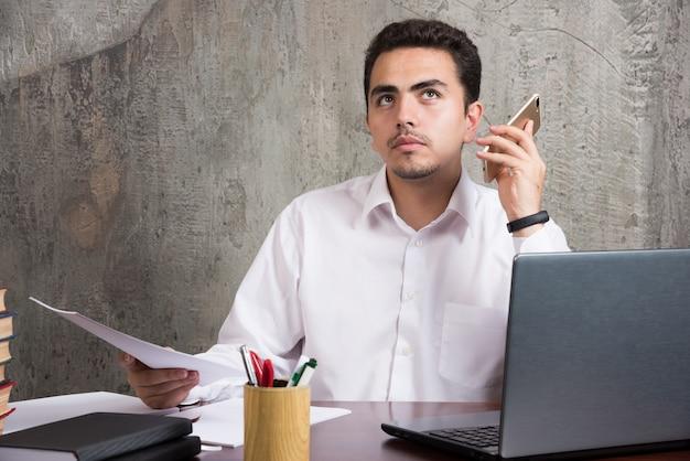 Poważny pracownik słuchający poczty głosowej z telefonu i siedzący przy biurku. wysokiej jakości zdjęcie
