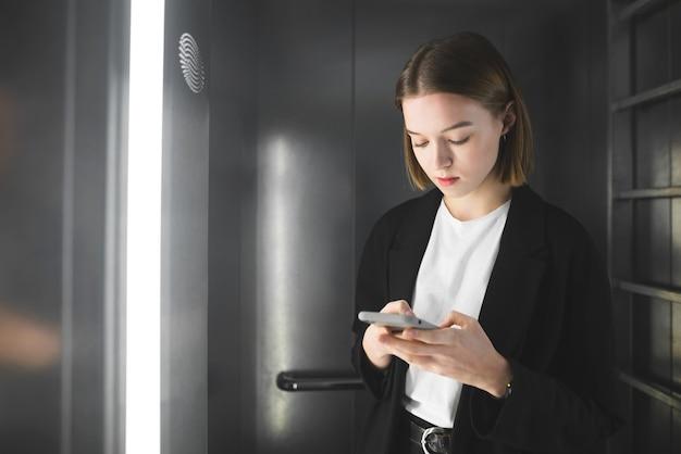 Poważny pracownik w czarnym garniturze sprawdza wiadomości na swoim smartfonie w windzie.