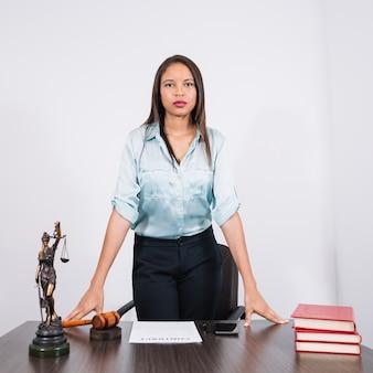 Poważny prawnik stoi przy stole z młotkiem i książkami