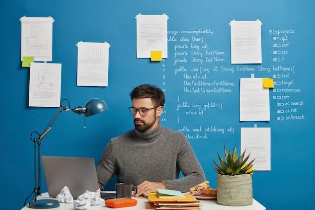 Poważny, profesjonalny maniak skupiony na monitorze nowoczesnego laptopa, nosi okulary optyczne, pozuje w przestrzeni coworkingowej na niebieskim tle