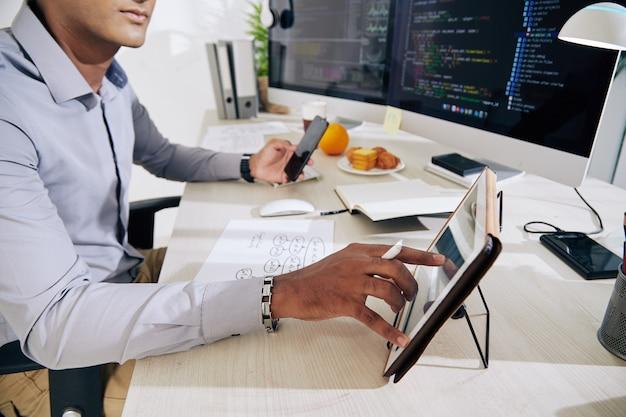 Poważny programista sprawdzający dane na cyfrowym tablecie, smartfonie i obu ekranach komputerów za pomocą kodu programującego