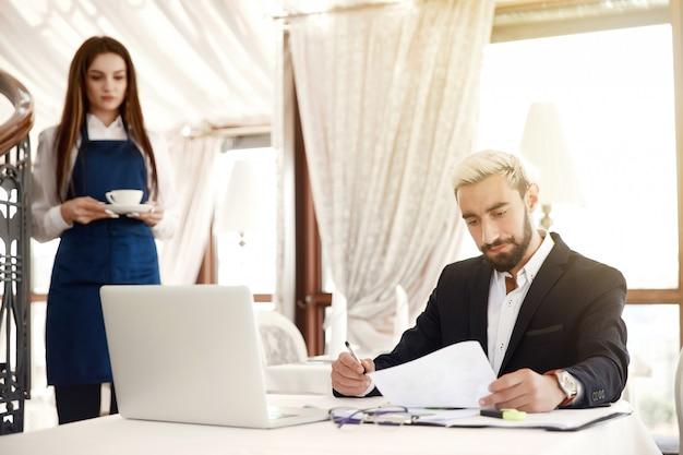 Poważny przedsiębiorca przegląda opinie finansowe, a kelnerka przynosi mu gorący napój