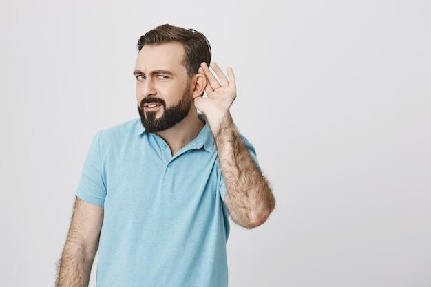 Poważny przystojny brodaty facet podsłuchuje, próbuje słuchać