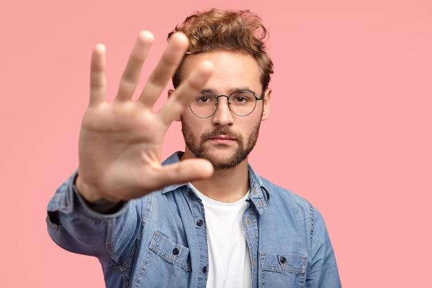 Poważny przystojny brodaty hipster wyciąga rękę w kierunku aparatu, pokazuje dłoń, demonstruje gest zatrzymania lub trzymania, nosi modne ubrania
