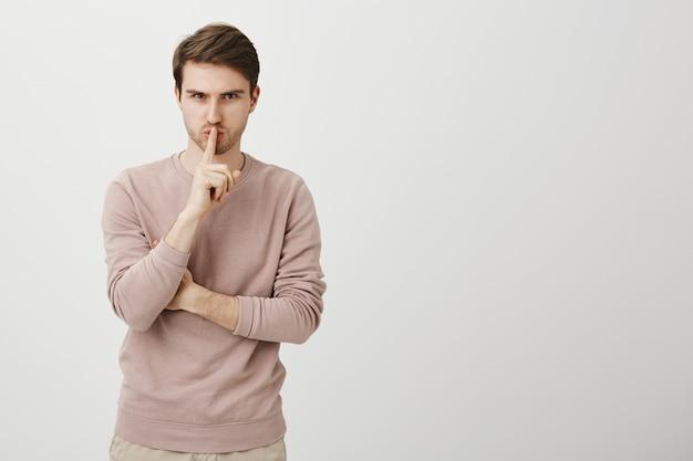 Poważny przystojny mężczyzna mówi: bądź cicho, uciszaj, zrób gest uciszenia
