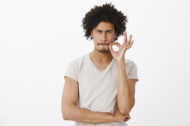 Poważny przystojny mężczyzna obiecuje nie mówić, zapinając usta na pieczęć