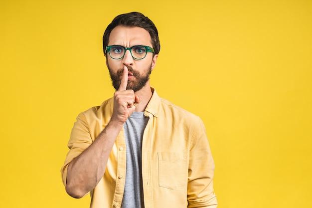 Poważny przystojny mężczyzna trzyma przedni palec na ustach, stara się utrzymać spisek. ciii, proszę, bądź cicho. atrakcyjny mężczyzna wykazujący znak ciszy izolowanych na żółtym tle.