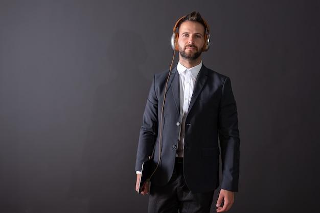 Poważny przystojny młody biznesmen w garniturze trzymając tablet i słuchając muzyki na szaro