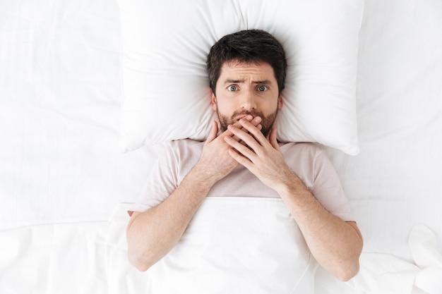 Poważny przystojny młody człowiek rano pod kocem w łóżku leży zakrywając usta