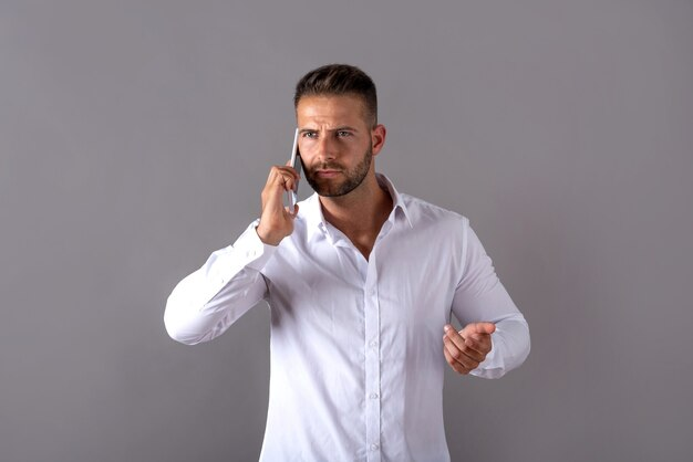 Poważny przystojny młody człowiek w białej koszuli rozmawia przez telefon i stoi na szaro