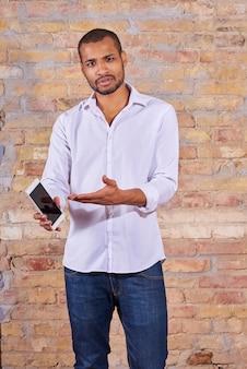 Poważny przystojny młody człowiek, wskazując na ekran swojego smartfona w białej koszuli.