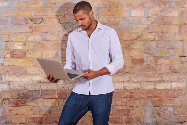 Poważny przystojny młody człowiek za pomocą laptopa w białej koszuli.