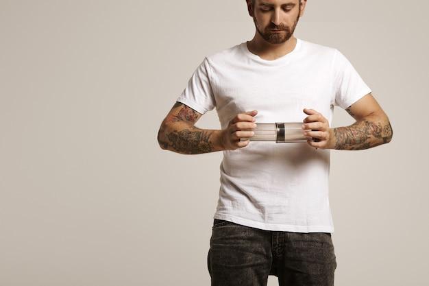 Poważny przystojny młody mężczyzna w białej bez etykiety t-shirt i dżinsach trzyma pusty aeropress