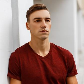 Poważny przystojny młody mężczyzna w modnej czerwonej koszulce ze stylową fryzurą stoi na zewnątrz w pobliżu zabytkowego białego budynku.