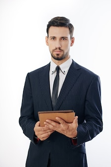 Poważny przystojny młody przedsiębiorca stojący z cyfrowym tabletem w ręce