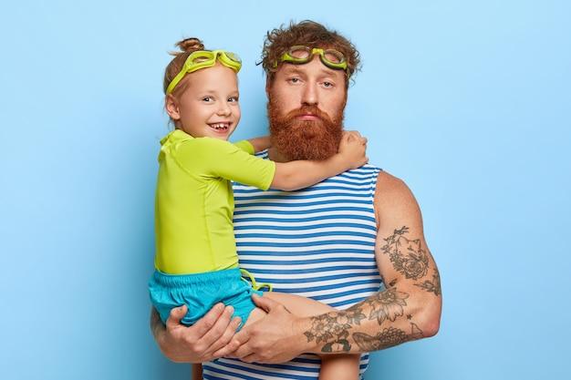 Poważny rudy mężczyzna czuje się zmęczony zabawą z dzieckiem, ubrany w letnie ubrania, nosi okulary pływackie, spędza razem wolny czas