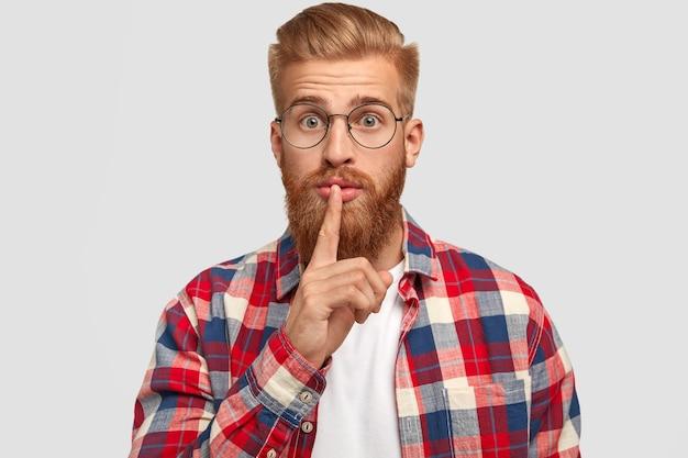 Poważny rudy mężczyzna, ma gęstą rudą brodę, trzyma palec wskazujący na ustach, wygląda skrycie, ma oszołomiony wyraz