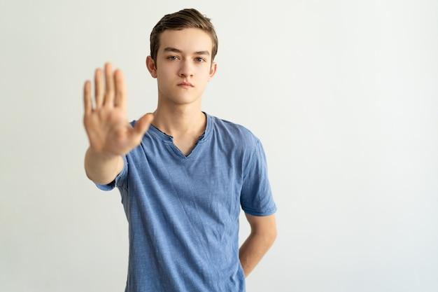 Poważny ścisły młody człowiek robi ograniczenie gestowi