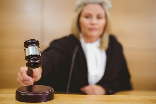 Poważny sędzia z młotkiem w szatach i peruce